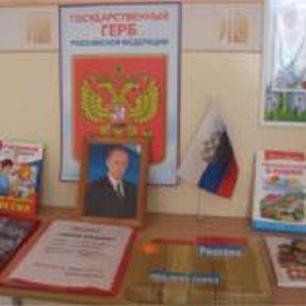Плакат с российским гербом, фото Путина, книжки и папки на столе