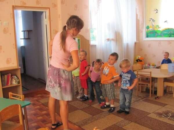 Малыши и педагог делают зарядку в помещении группы