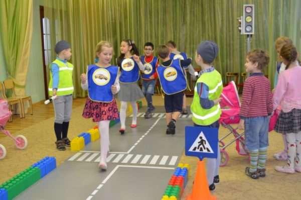 Дети в костюмах дорожных знаков, регулировщиков разыгрывают сюжет в декорациях проезжей части