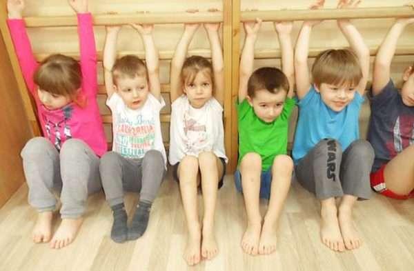 Дети держатся за нижние рейки гимнастической стенки