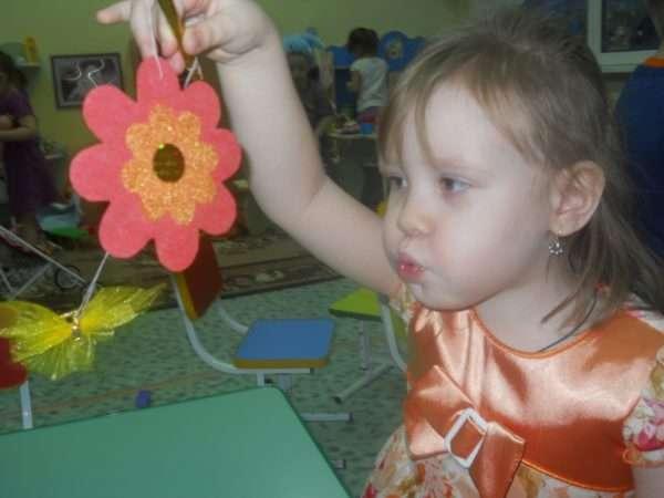 Девочка дует на бумажный цветок и бабочку