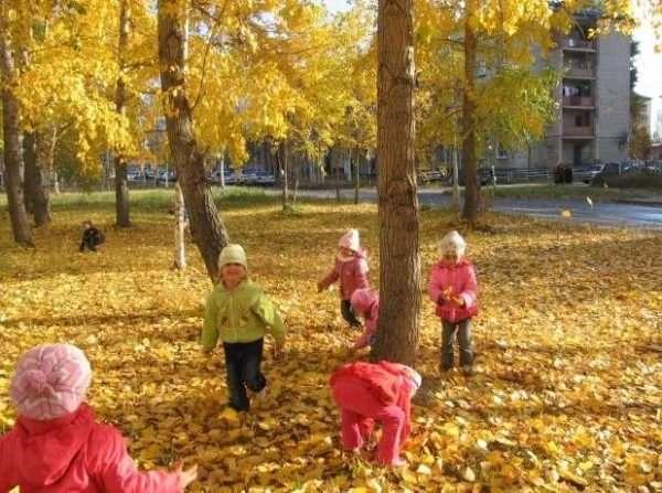 Дети играют в осенней листве