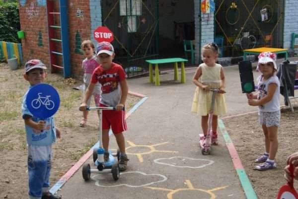 Мальчик держит разрешающий знак для велосипедистов, мальчик в красной футболке и девочка в жёлтом платье едут на самокатах