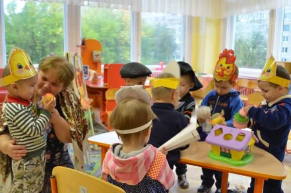 Педагог и малыши в масках-шапочках