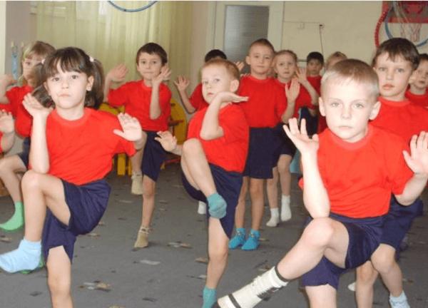 Дети в спортивной форме делают упражнение, поднимая колено к локтю