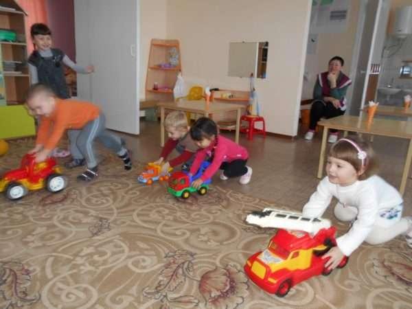 Дети катают большие машинки по ковру