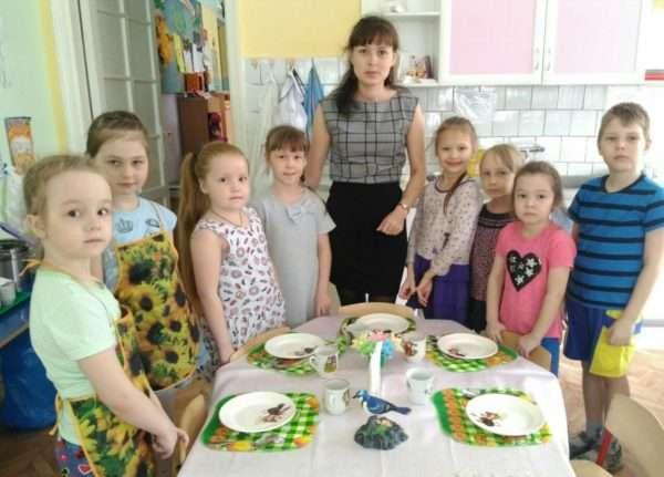 Педагог и дети перед сервированным столом