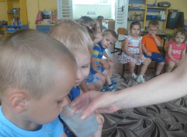 Ребёнок пробует на вкус воду, разведённую с соком