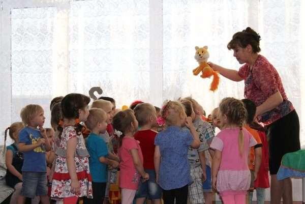 Воспитательница показывает детям игрушку-лисичку