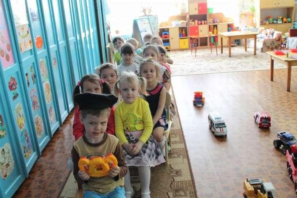 Дети играют пассажиров автобуса, мальчик-шофёр держит игрушечный руль