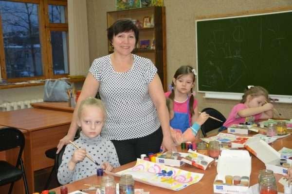 Дети рисуют красками, воспитатель стоит рядом
