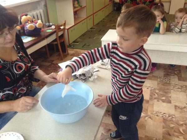 Мальчик опускает мокрую салфетку в таз с водой