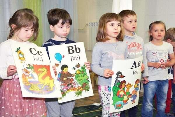 Дети держат картинки с английскими буквами