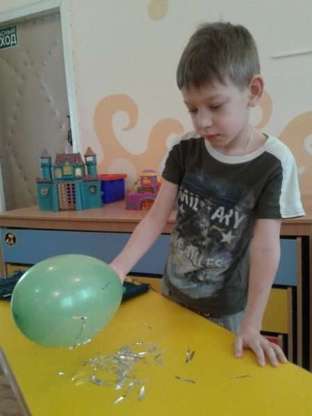 Мальчик проводит эксперимент с воздушным шариком и фольгой