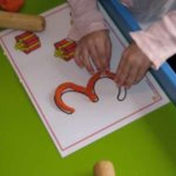 Ребёнок лепит пластилиновую цифру 3