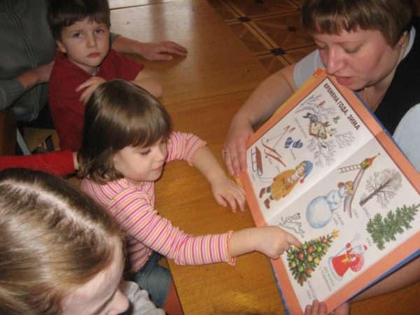 Девочка показывает на ёлочку в книге, которую держит воспитательница