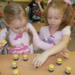 Две девочки играют с контейнерами из-под киндер-сюрпризов
