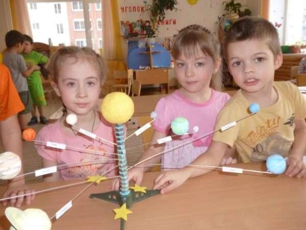 Трое детей стоят рядом с макетом Солнечной системы
