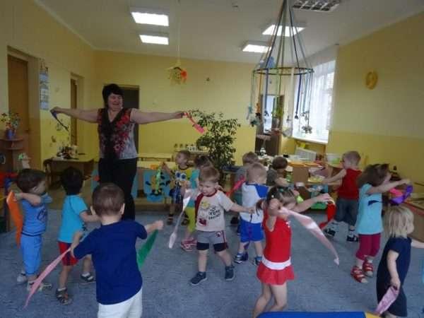Воспитательница и дети в группе размахивают лентами на ходу