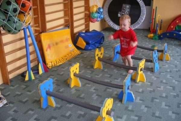 Мальчик в красной футболке в спортзале бежит через препятствия