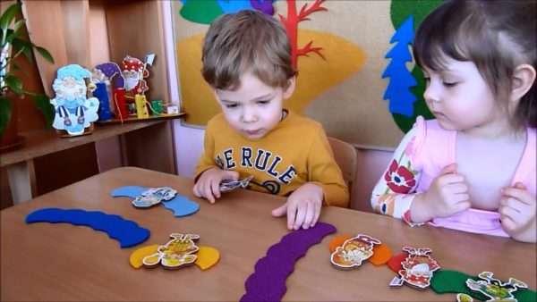 Мальчик и девочка крепят фигурки на цветные дуги