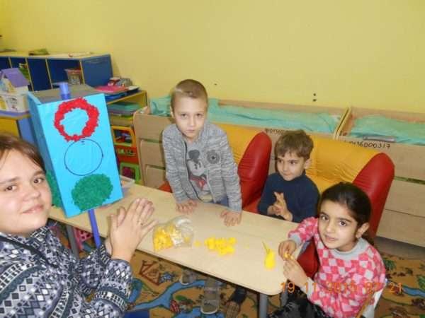 Четверо детей работают над поделкой светофора в технике пластилинографии