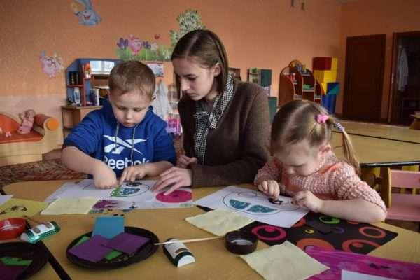 Педагог помогает детям выкладывать аппликацию из кусочков