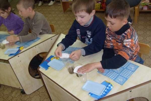 Дети проводят опыт с водой и бумагой
