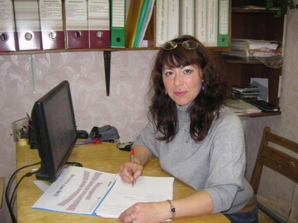 Воспитатель сидит перед ноутбуком и делает пометки на листах в папке