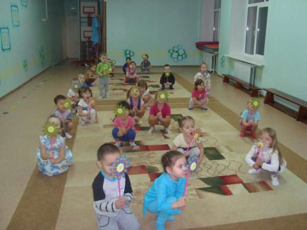 Дети сидят на ковре и дуют на вертушки