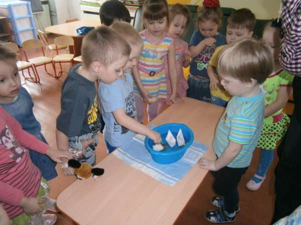 Группа детей наблюдает за плавающими в синем тазу бумажными корабликами