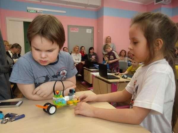 Мальчик и девочка на занятии собирают машинку из деталей