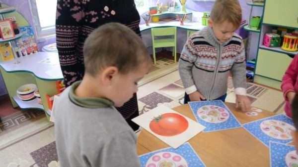 Два мальчика стоят около стола, на котором картинки с овощами