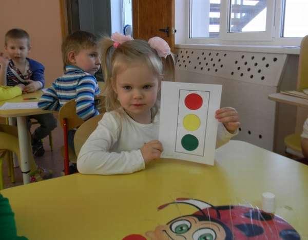 Девочка держит картинку с сигналами светофора