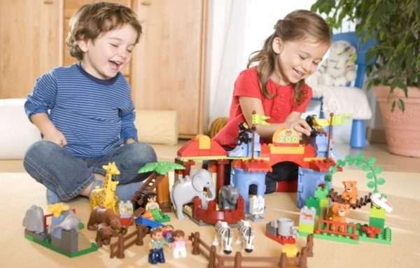 Мальчик и девочка играют с конструктором на полу