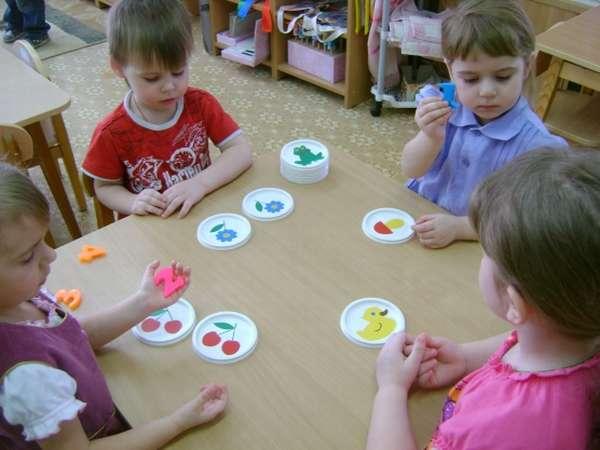 Ребята сидят вокруг стола, на котором лежат цветные картинки с предметами и пластмассовые цифры