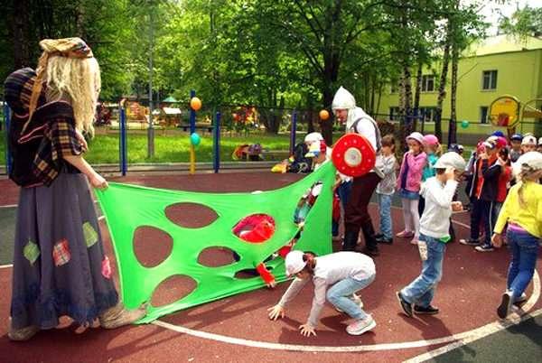 Дети на площадке играют в подвижную игру, организованную сказочными персонажами