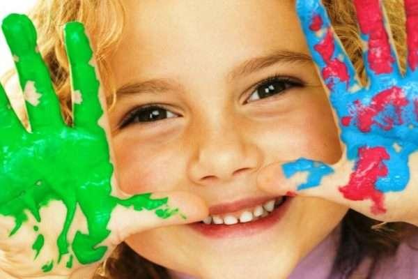 Девочка показывает ладошки в красках
