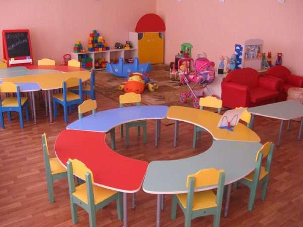 Круглый стол из четырёх сегментов, стулья, на заднем плане два красных кресла