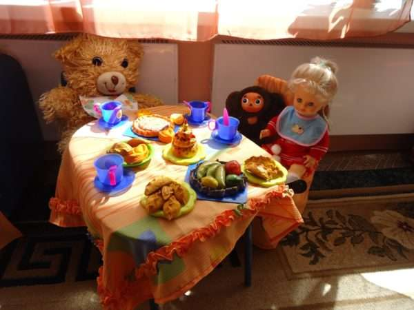 Кукла и игрушки за обеденным столом
