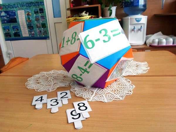 Многоугольник с математическими примерами, на столе лежат карточки с цифрами