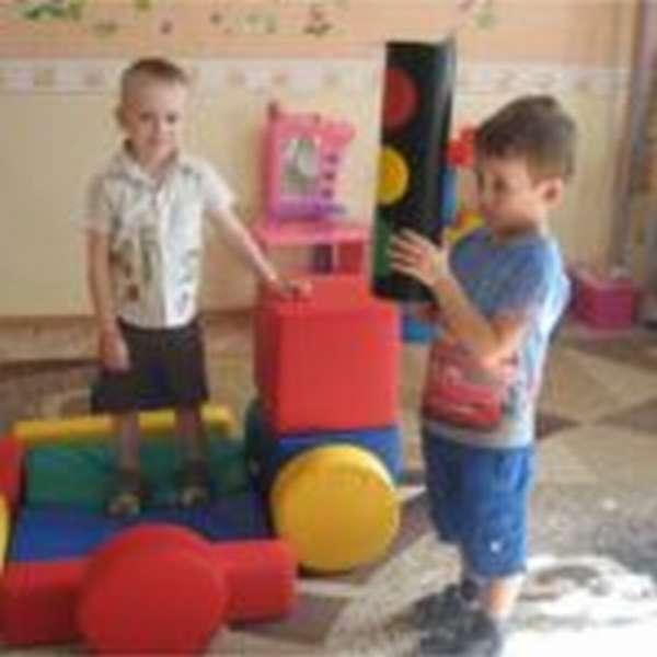 Один мальчик стоит на больших деталях мягкого конструктора, второй держит элемент игрушки — светофор