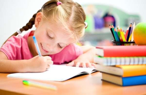Девочка пишет в тетради