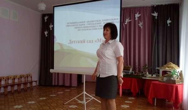 Воспитатель выступает с докладом, на заднем фоне — экран с презентацией