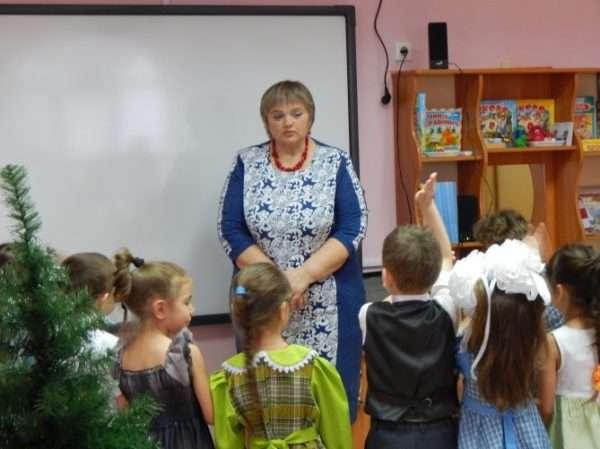 Воспитательница стоит у доски, перед ней полукругом выстроились дети