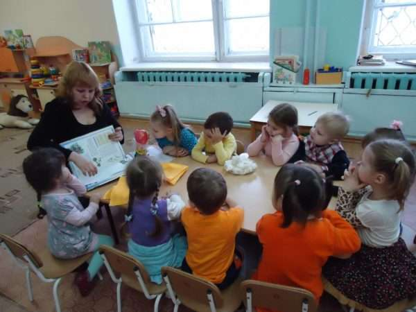 Воспитатель показывает детям за столом книжку