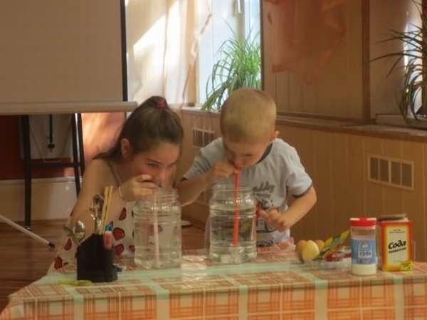 Мальчик и девочка дуют в трубочки, погружённые в банки с водой
