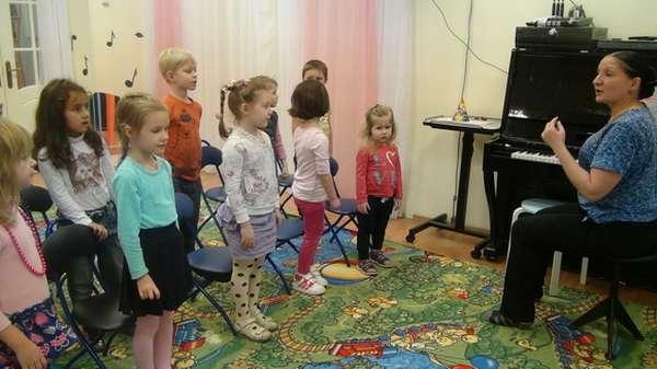 Педагог сидит за фортепиано, дети перед ним поют
