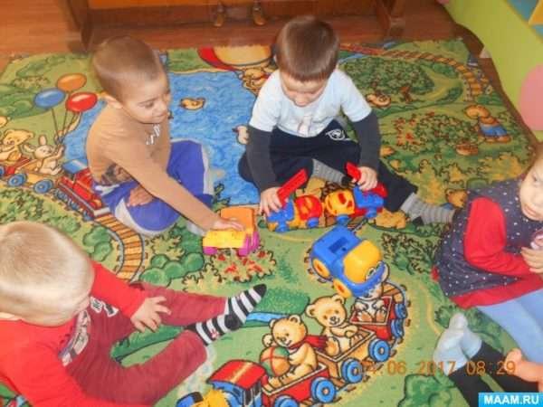 Дети играют с машинками на ковре