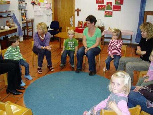 Дети и воспитатель сидят по кругу, взрослый что-то рассказывает